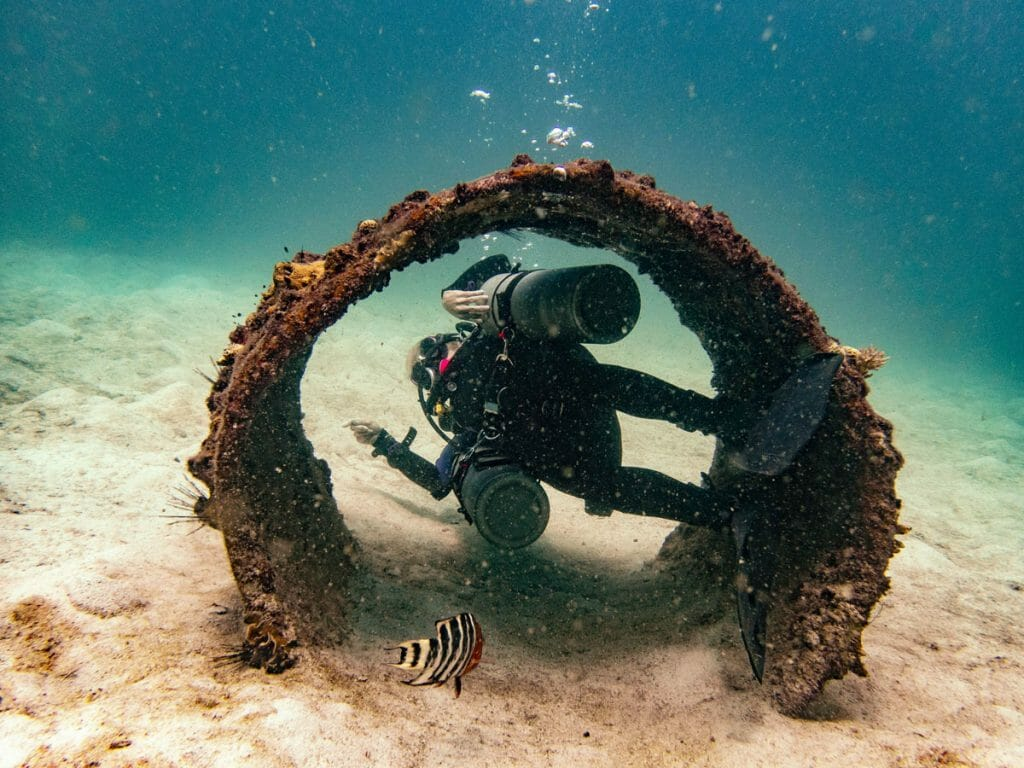 Sidemount diver going through a tube