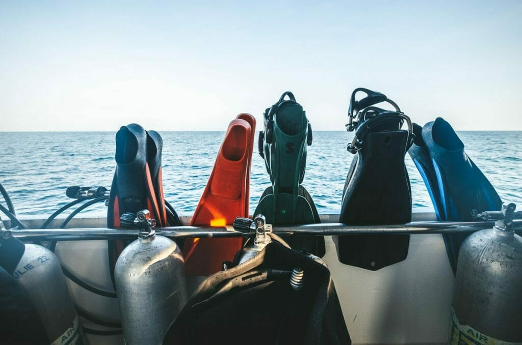 Various scuba fins on a railing